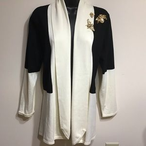 Cyrus jacket embellished with three gold pins.